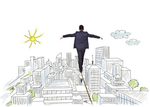 businessman balancing on tightrope city