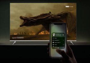 Pantalla de tv plana con la imagen de un dragón. Frente hay un celular que lo controla.