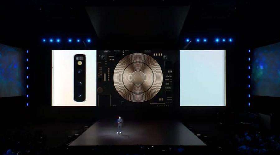 """Un hombre en un escenario oscuro con una pantalla gigante detrás, presenta el beneficio de """"carga inalámbrica e invertida"""" del dispositivo."""