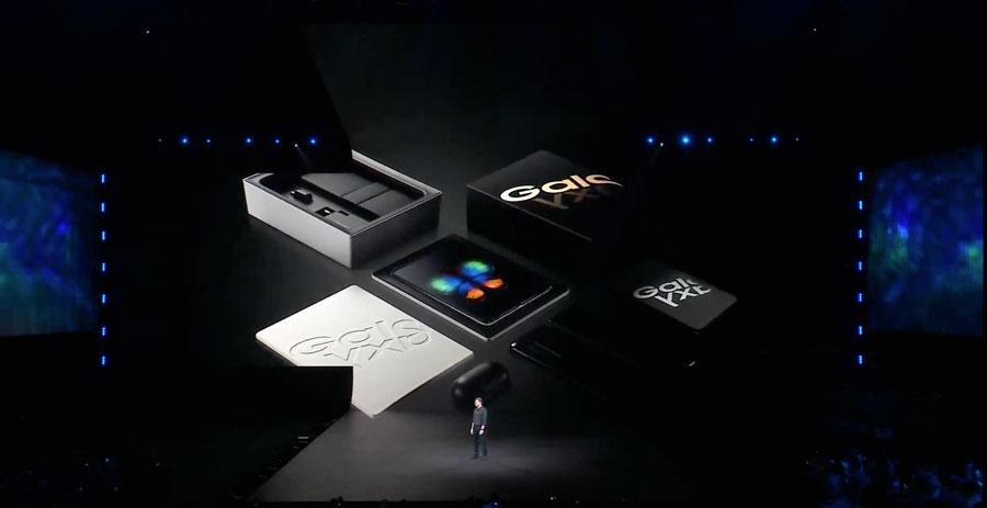 Hombre en un escenario oscuro, con una pantalla gigante detrás, presentando el nuevo Galaxy Fold.