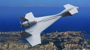 Dron con apariencia entre misil y avión, de color gris, que sobrevuela un terreno.
