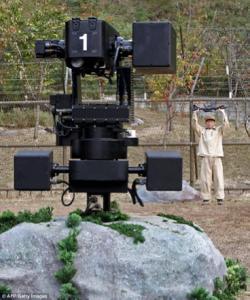 Robot negro tipo ametralladora que tiene su soporte sobre una roca y apunta a una persona.