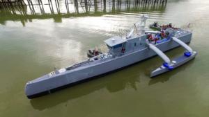 Buque de guerra tipo lancha gigante de color azul que navega sobre un río.